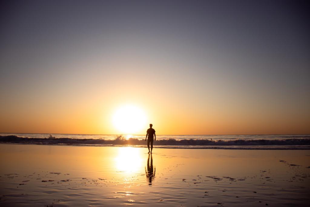 海に沈む太陽と人