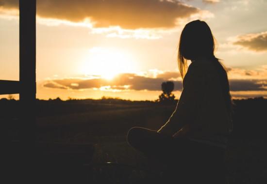 地平線の太陽を見る人