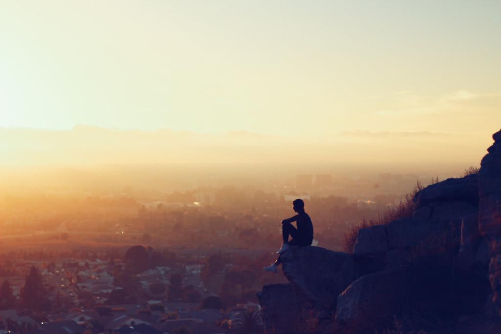 山から街を見渡す人