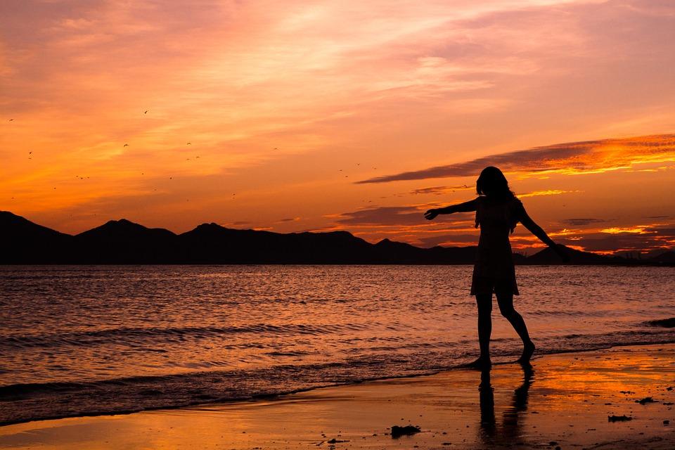 夕焼けの海を散歩する人