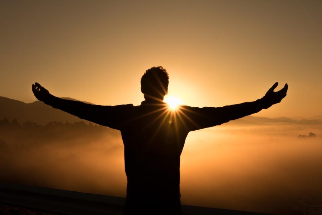 太陽の光を全身で受ける人