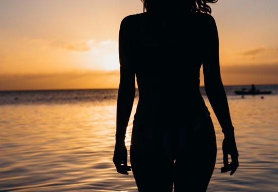 朝日の昇る海と人