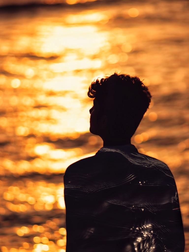 太陽が反射する海を見る人
