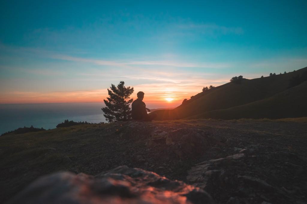 山頂から太陽を見る人