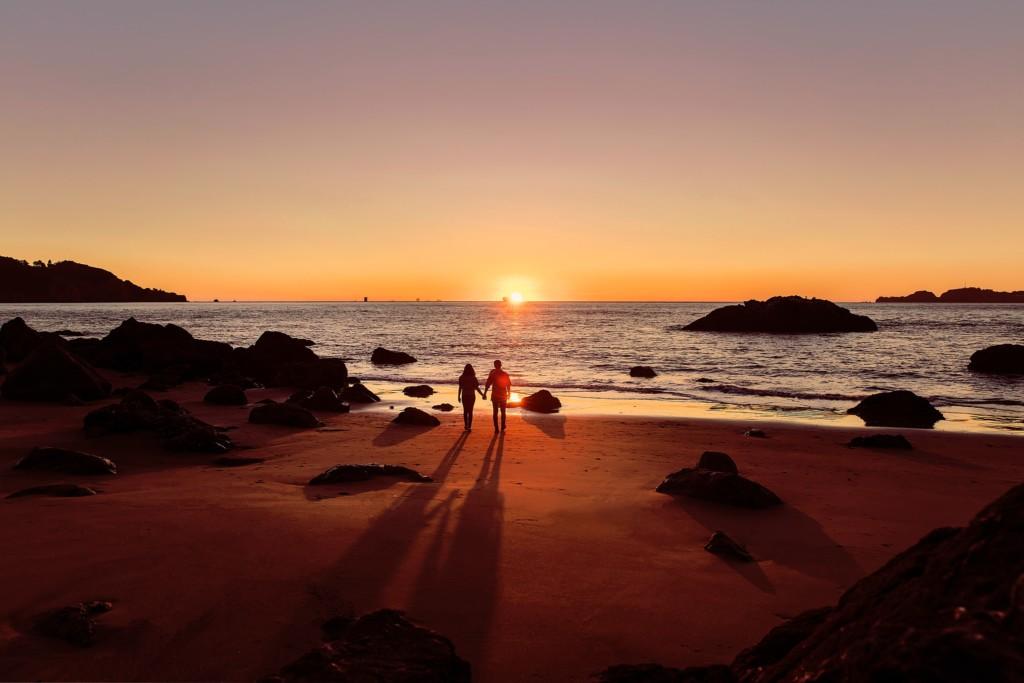 朝日の昇る海岸と人