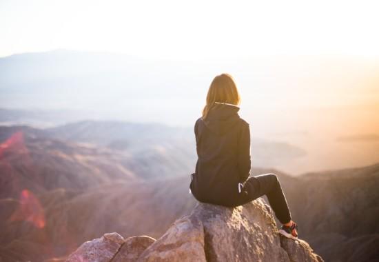 山頂から朝日を見る人