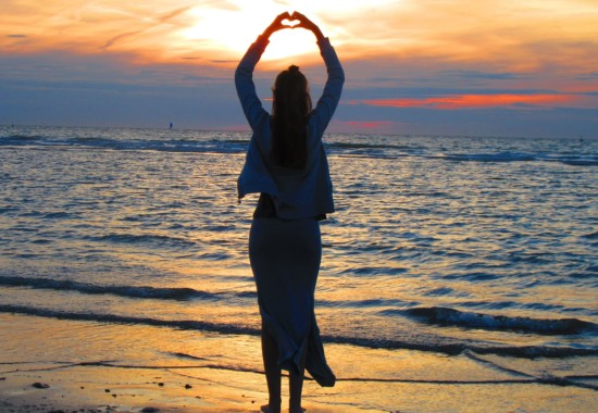 太陽の昇る海岸と人