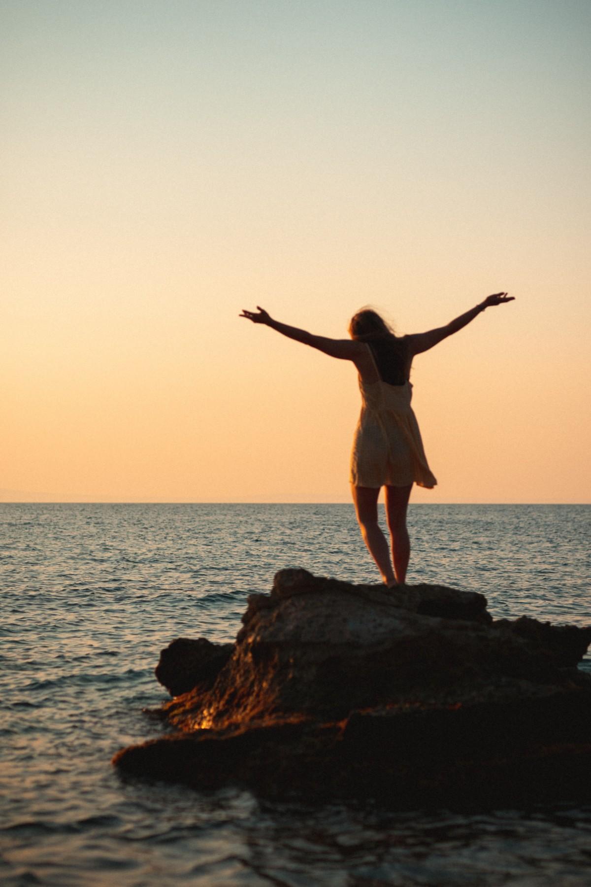 海から昇る太陽を見る人