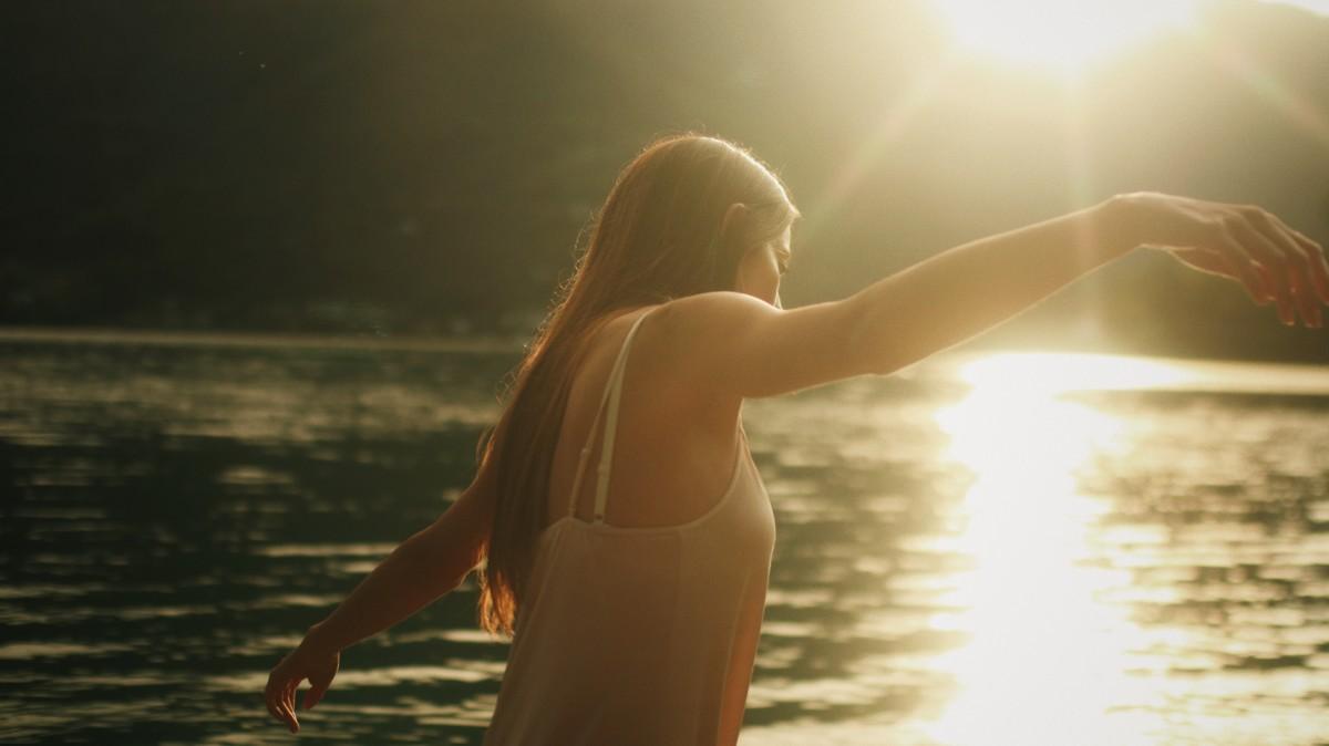 太陽が反射する湖と人