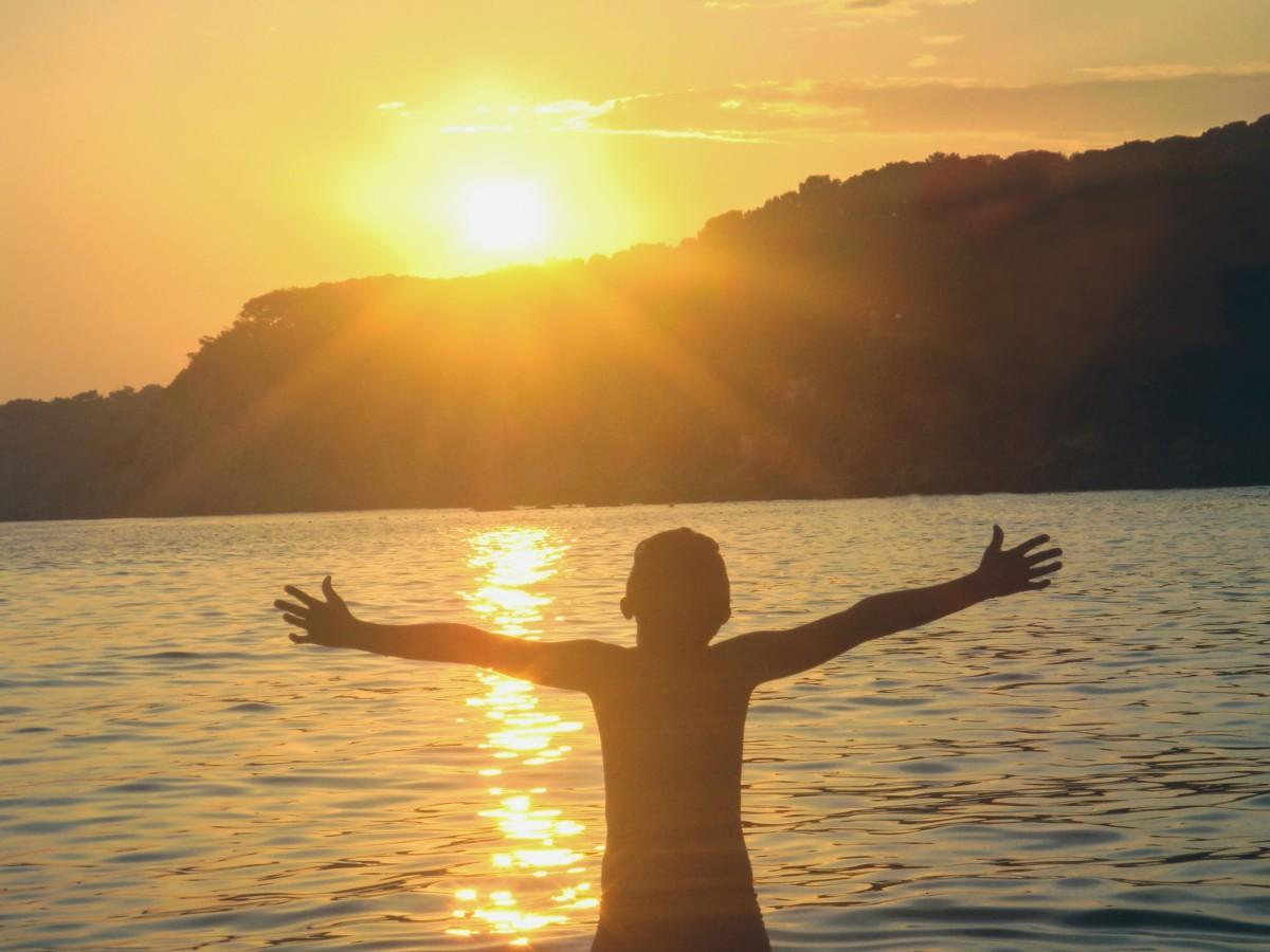 太陽に向かって両手を広げる人