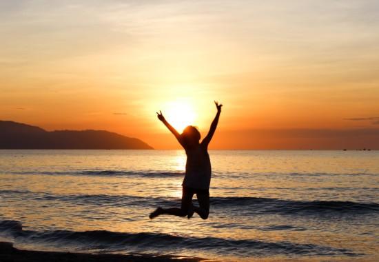 朝焼けの海でジャンプする人