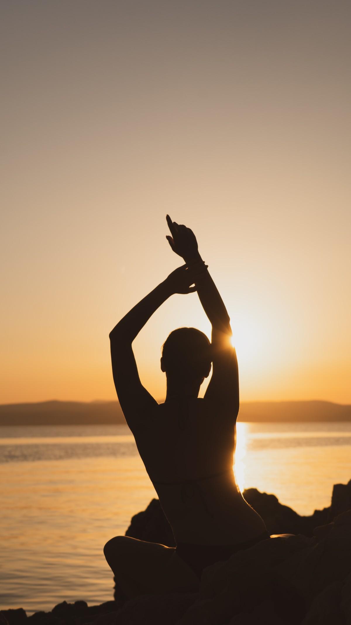 朝焼けの海を見つめる人